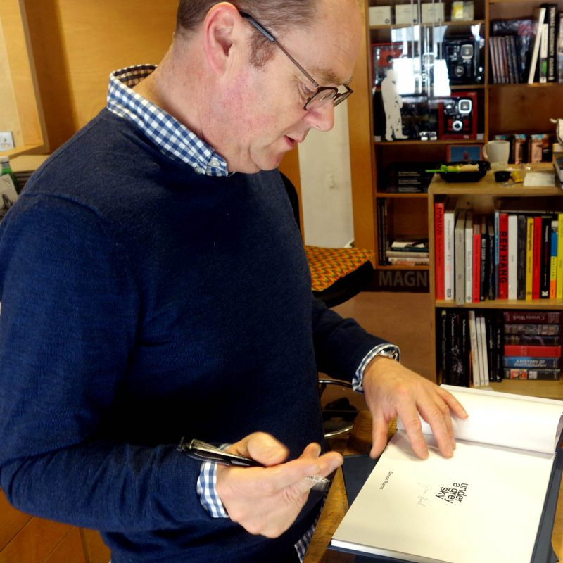 Artist Simon Burch signing copies of Under a Grey Sky