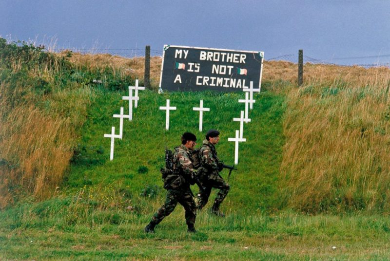 Patrolling British soldiers pass a memorial to IRA hunger strikers in the region known as 'Bandit Country'. The main movement of the army in this area was by air due to the risk of being targeted by the IRA, Crossmaglen, South Armagh, 1985, by kaveh kazemi